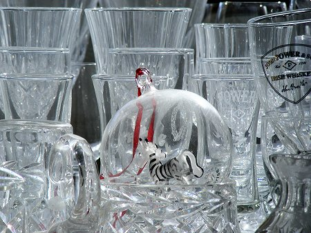 Zebra in a Glass Christmas Ornament surrounded by whiskey and wine glasses