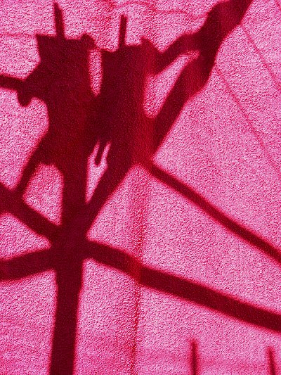 Shadows of a whirly clothesline through a drying towel