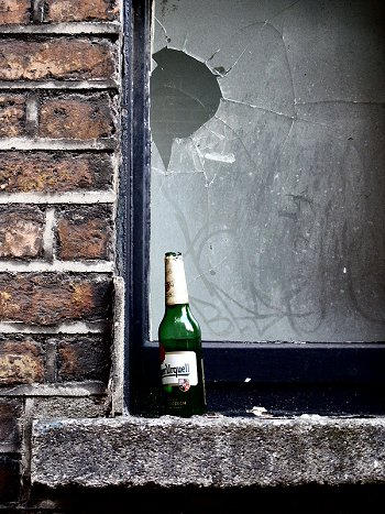 an empty bottle of Pilsner Urquell on a window sill in Dublin, Ireland