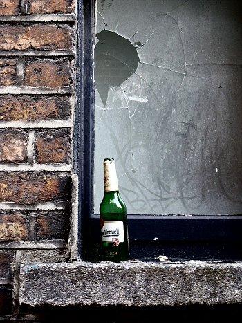an empty bottle of Pilsner Urquell on a window sill in Dublin, Ireland