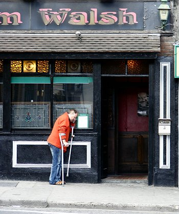 Man on crutches on phone outside Dublin pub