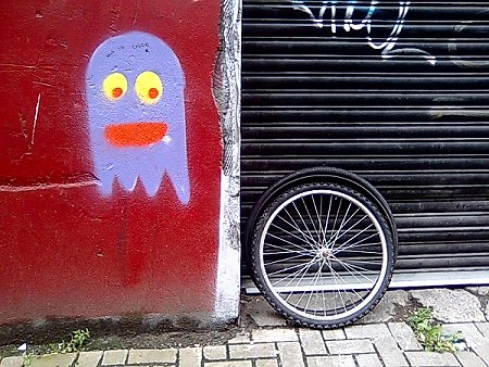 A graffiti Pac Man eyes up a loose bicycle wheel and tyre